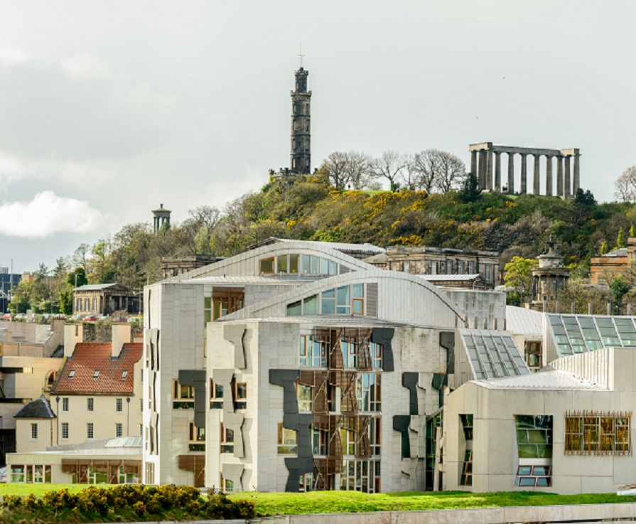 The Scottish Parliament buiilding with Calton Hill in the background